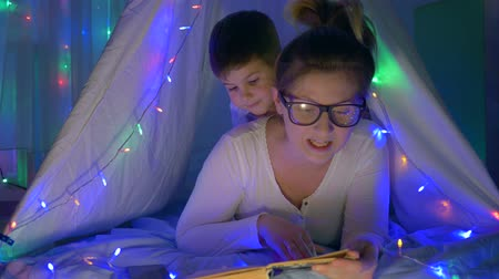 festoon : mother-child relationship, mum in glasses reads to toddler book before bedtime lying in tent with vivid lights at home at night Stock Footage