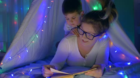petite : maternal care, young mama and son reading book lying in tent with bright festoon indoors in evening