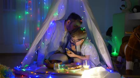 festoon : male gossip, Dad tells child secrets during dinner after dinner in teepee with festoon indoors in evening