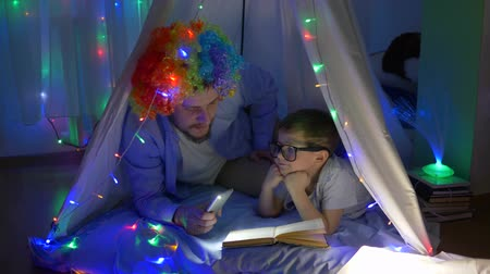 festoon : home entertainment, happy kid with papa into funny wig reading book in light of flashlight lying at magical tent with garlands in evening