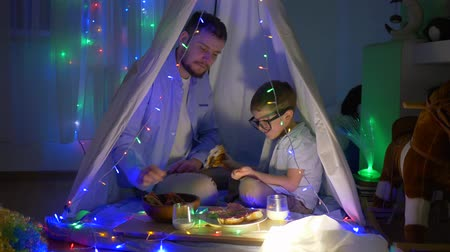 festoon : happy childhood, daddy with son eating buns sitting in tent decorated with garlands at night indoors in evening