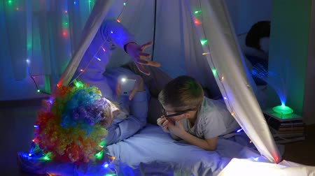 festoon : family leisure, cheerful child with papa in clown wig and tells terrible stories lying in tent with bright lights Stock Footage