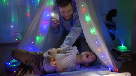 festoon : family fun, father tickling toddler in children tent with vivid lights at night in weekend