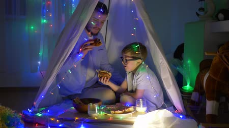 petite : evening cheerful meal, papa with boy eating bakery products sitting in tent decorated with garlands at children room at night