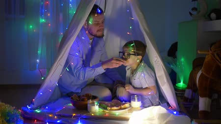 festoon : children dinner, father with kid eat sandwiches in teepee with bright garlands at home at night