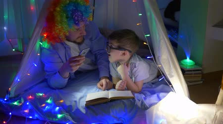 книга : cheerful clown reads magazine with kid before going to bed in magical tent with garlands at children room in dark Стоковые видеозаписи