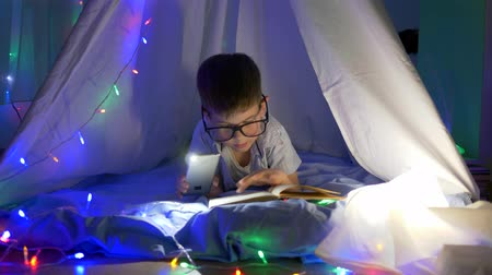 petite : book reading, clever kid into spectacles reading fairy tales in flashlight lighting lying into tent with garlands at home in evening