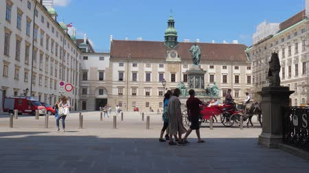 talapzat : Vienna, Austria 20 May 2018: horse-drawn carriage with tourists on background of Monument of Kaiser Franz I and architectural objects of old city in Vienna, 20 May 2018. Stock mozgókép