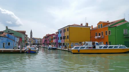 типичный : Burano, Italy 19 May 2018: cityscape, colorful houses near water with motor boats on background sky in Burano, 19 May 2018. Стоковые видеозаписи