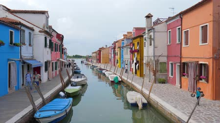 burano : Burano, Italy 19 May 2018: motor boats on water canal among color architecture in Burano, 19 May 2018. Stock Footage