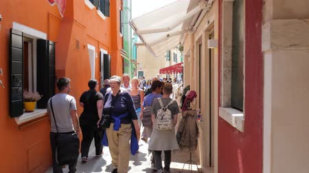 burano : Burano, Italy 19 May 2018: people walk along long street with shop windows and choose souvenirs in Burano, 19 May 2018. Stock Footage
