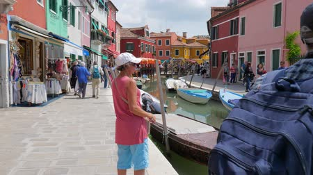 burano : Burano, Italy 19 May 2018: people walk to town street along water canal with motor boat and colored buildings in Burano, 19 May 2018.