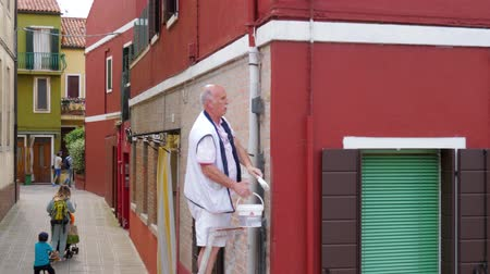 типичный : Burano, Italy 19 May 2018: repair of house, elderly man paints wall of building on street in Burano, 19 May 2018. Стоковые видеозаписи