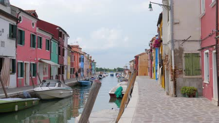 burano : Burano, Italy 19 May 2018: water canal with motor boats among colored houses in Burano, 19 May 2018. Stock Footage