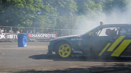 peril : Kiev, Ukraine 23 May 2018: extreme auto competition, car performs drift on fenced area on fenced area in front of people in Kiev, 23 May 2018. Stock Footage