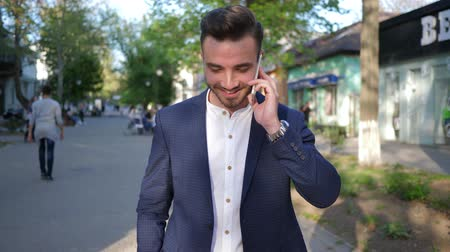 smokin : Kherson, Ukraine 22 April 2018: attractive male talking on mobile phone while walking outdoors in Kherson, 22 April 2018.