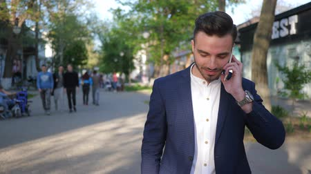 telefon : Kherson, Ukraine 22 April 2018: handsome guy talking on cell phone while walking down city street in Kherson, 22 April 2018.