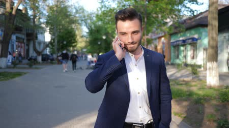 gentleman : Kherson, Ukraine 22 April 2018: mobile communication, young man talking on smartphone while walking down street town in Kherson, 22 April 2018.