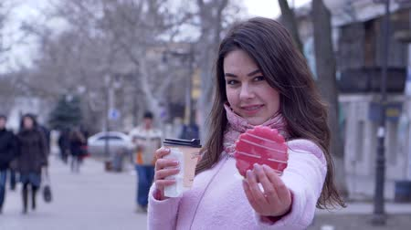 desfocado : sweet tooth, hungry girl with pastry and warming drinks in plastic cup outdoors in city close-up Stock Footage