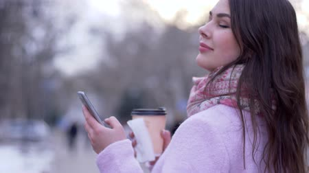 arms in the air : smartphone and tea in plastic cup into hands of women close-up on open air on an unfocused background Stock Footage