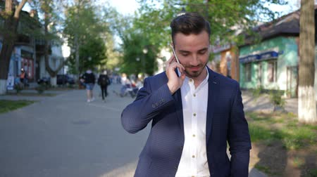 telefon : business man talking on mobile phone while walking down street city close-up on unfocused background Stock mozgókép