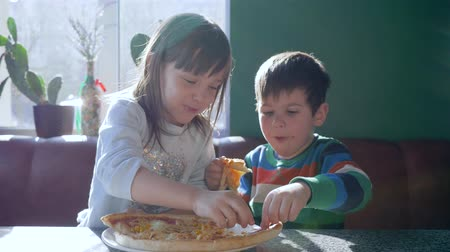 petite : food time, little girl with pizza feeds boy during dinner in dining room near window at holiday