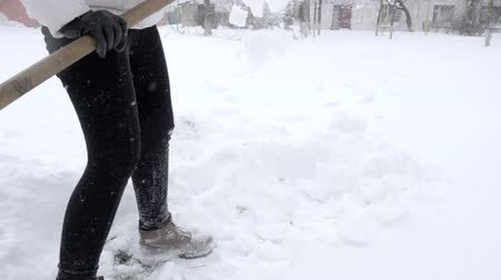 ciclone : shoveling snow, janitor with spade cleans snowdrift in winter close-up Stock Footage