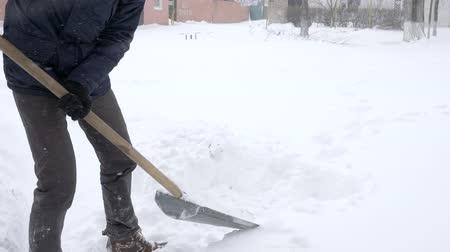 binnenhof : sneeuwruimen, man met schop in de hand reinigt tuin van sneeuwbanken in de winter close-up Stockvideo