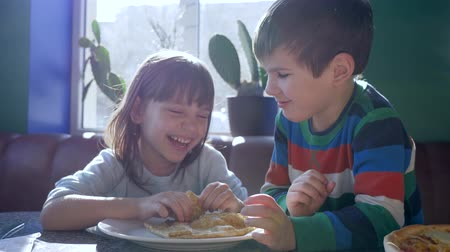 блин : tasty food, happy children eat pancakes for breakfast in restaurant with vivid natural light