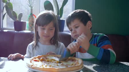 petite : tasty food, happy children cut pizza into pieces during dinner in canteen on background of window at weekend Stock Footage