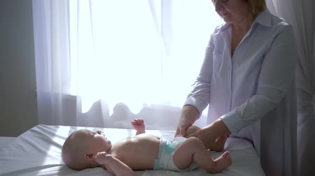 младенчество : female physiotherapist massages the feet of newborn on table near window in room
