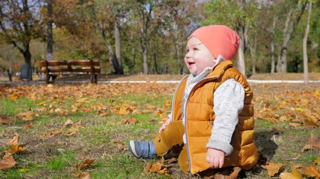 salya : happy child with saliva smiling outdoors sitting on lawn with yellow leaves in autumn city park Stok Video
