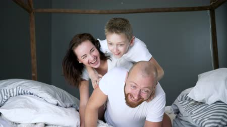 identical : young woman with her son and husband relaxing on the bed, very happy family moments