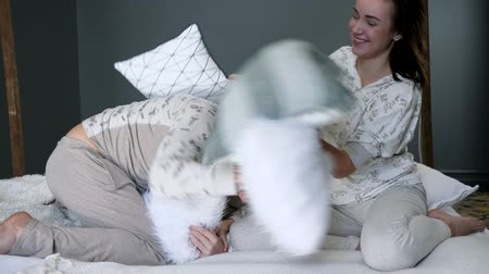 пижама : happy family in identical pajamas beat each other with pillows on the bed close-up in studio on photo shoot