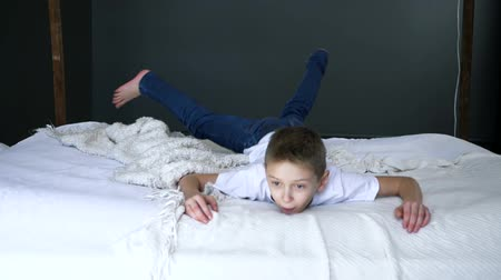 caráter : entertainment, happy boy runs and jumps on the bed in slow motion at bedroom