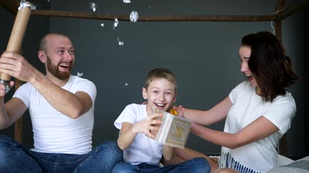 white shirt : happy boy is holding a present in hands near mom while young father is blowing up cracker with confetti