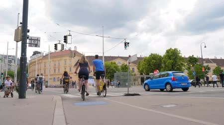 cuidado : Vienna, Austria 20 May 2018: cyclists wait green signal at city crosswalk and then cross the road in Vienna, 20 May 2018.
