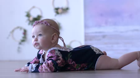 korale : baby life, cute infant lies on floor and looks into distance indoors close-up on unfocused background Wideo