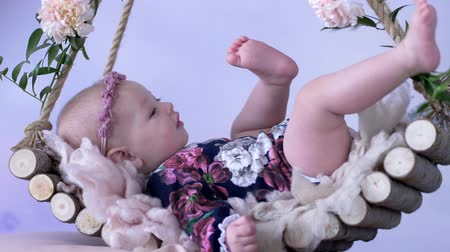 korale : nice baby lies in wooden swing decorated with flowers on white background close-up