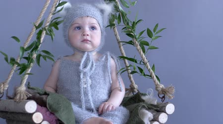 knitted : cute infant in squirrel suit is sitting on vine swing decorated with greenery on blue background close-up