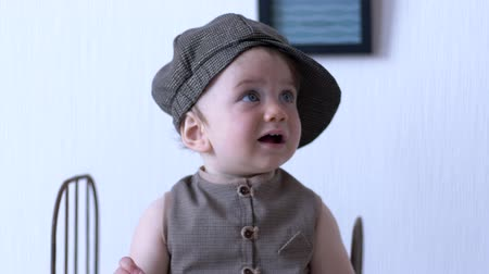 petite : Fashionable child, cute infant in stylish suit looks around against white wall in room Stock Footage