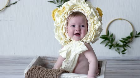 круглолицый : laughing baby boy in headdress sit in wooden box and poses at camera on photoshoot closeup