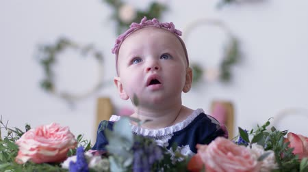 frizura : baby girl look up with open mouth sit in flowers on photo shoot in studio with decoration close-up