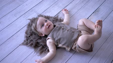 pelyhes : funny child lies and wiggles legs on wooden floor close-up