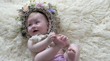 frizura : childhood, baby in hoop with flowers lies on rug and poses at camera on photoshoot closeup