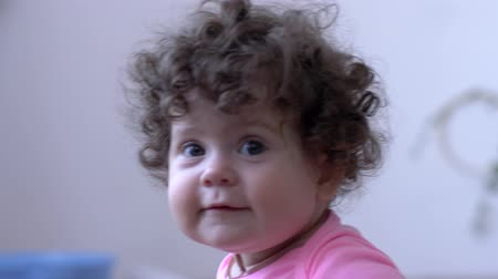 desfocado : happy infant with curls is played indoors close-up on unfocused background