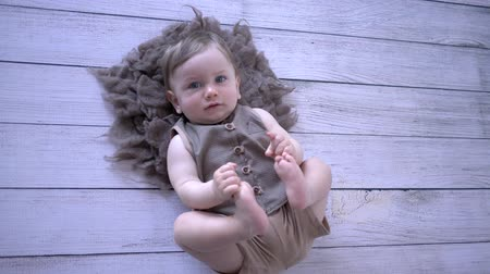 pelyhes : infant life, cute baby lies and pulls legs on wooden floor close-up