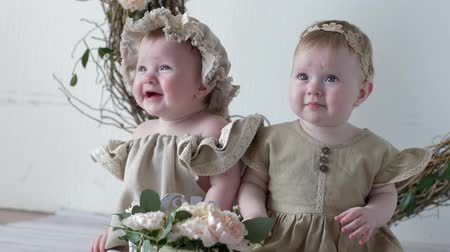 круглолицый : birthday sisters in dresses sitting on photo shoot in studio on background of wall with decor