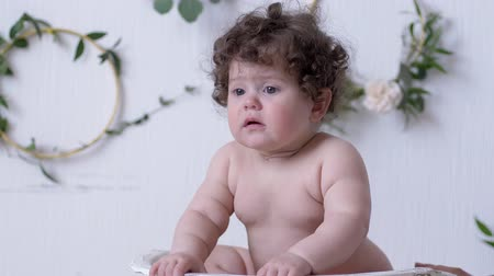 baby chubby : upset child posing on a photo session in studio on background of white wall with decor
