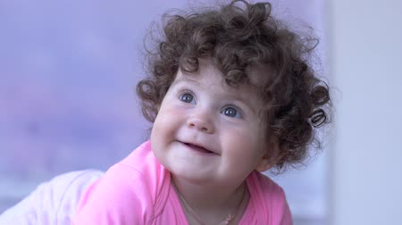 desfocado : smiling toddler with curly hair spends time in room close-up on unfocused background Stock Footage